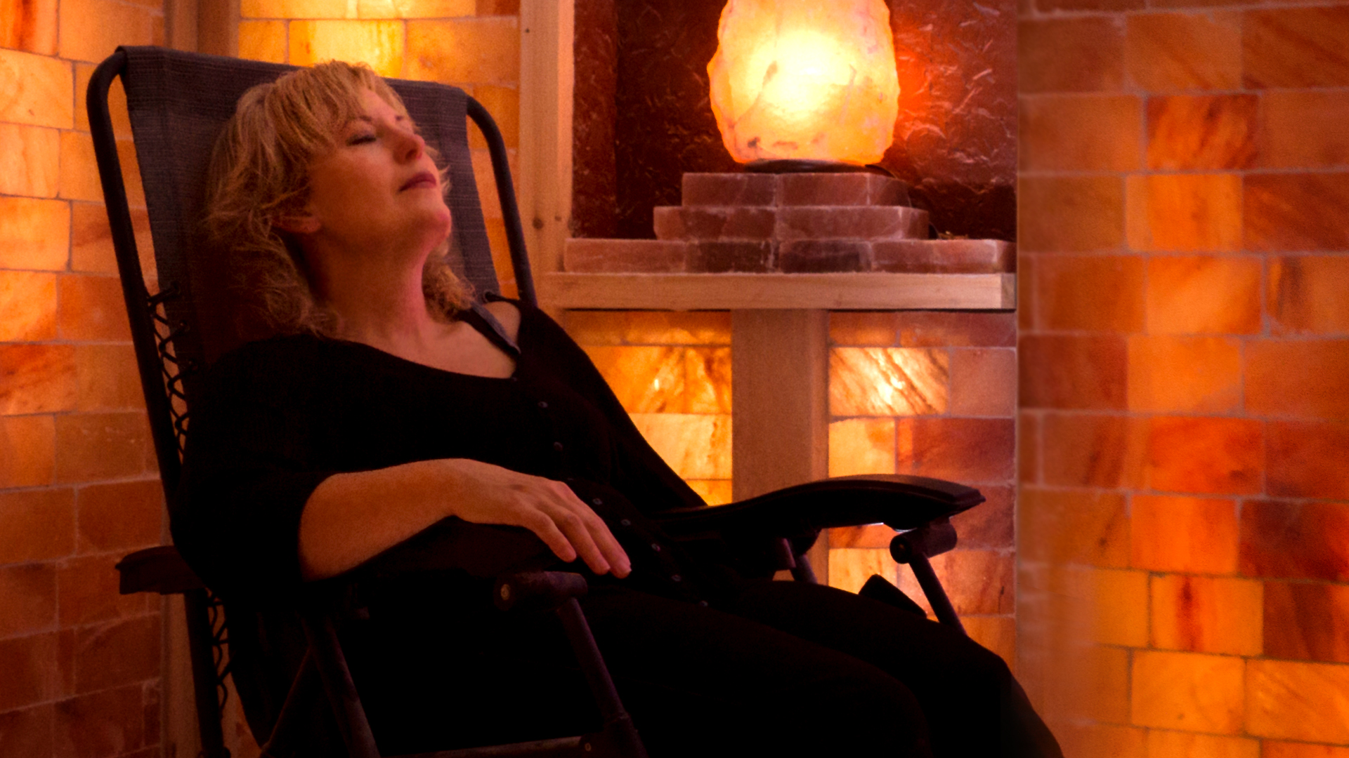 adult old blonde woman leaning back in chair at himalayan salt cave, relaxing and meditating