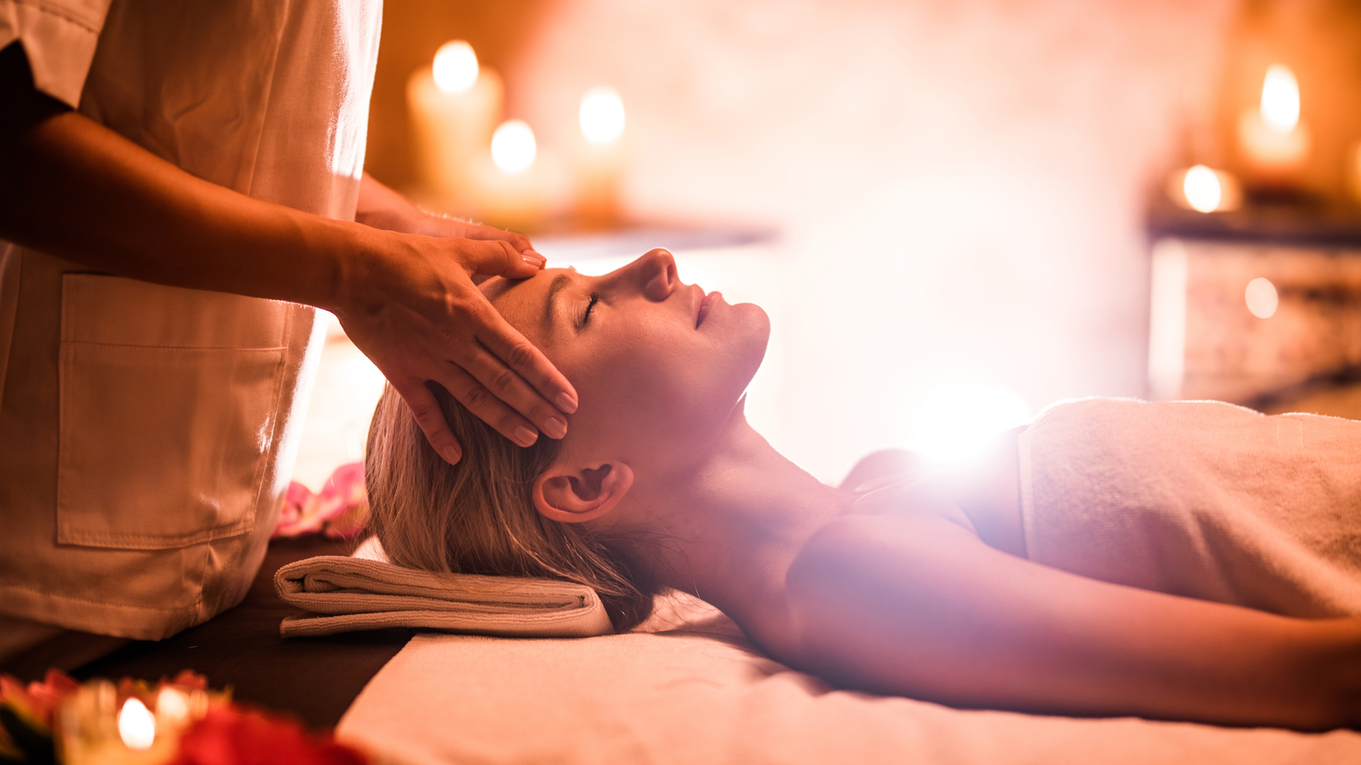 young blonde mom woman laying on massage table in towel, reiki master performing reiki